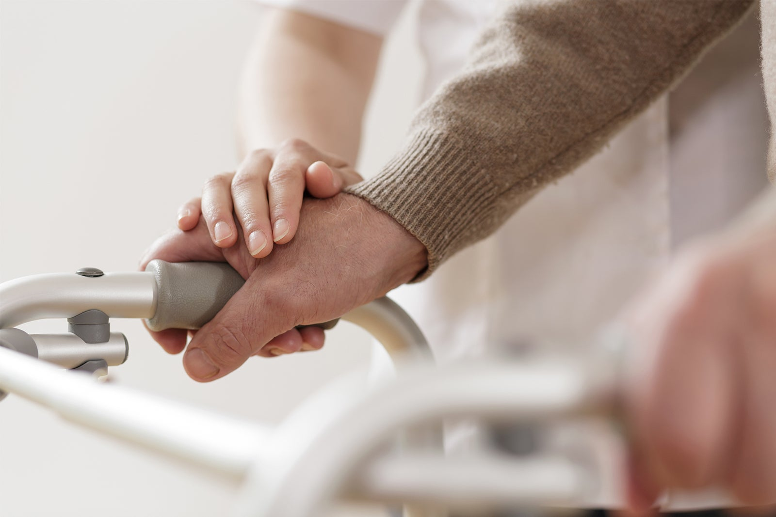 A caring hand placed on the hand of an older man who is holding onto his walker handles.