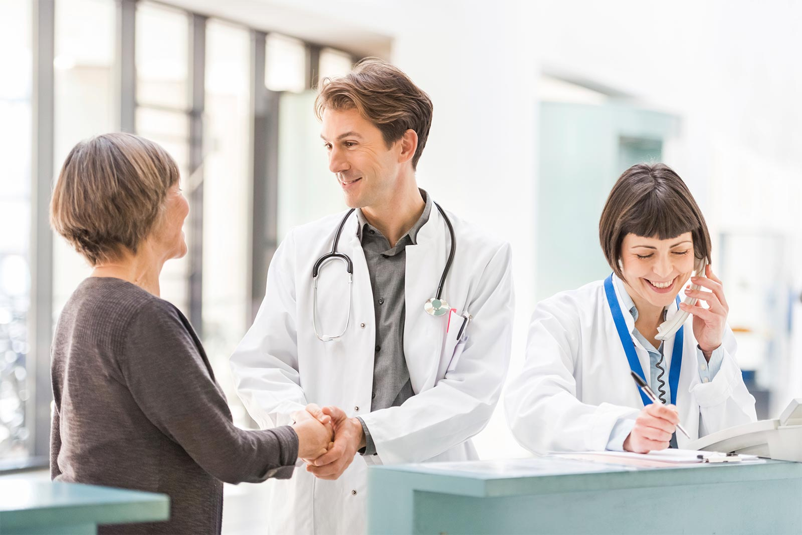 A doctor shaking hands with a patient, and another doctor talking on the phone, in a medical office.