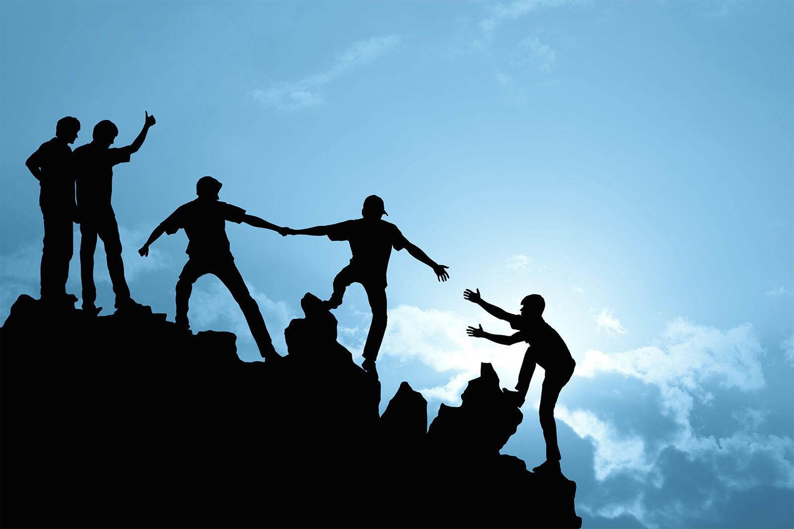A team of 5 people helping each other climb a mountain.
