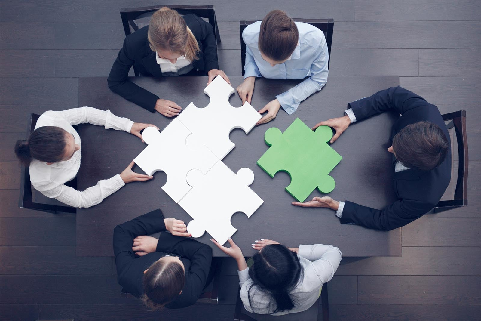 Group of business people putting together overly large puzzle pieces.