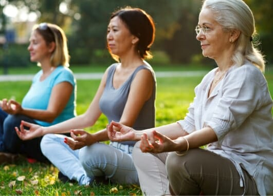 Three women outdoors in seated yoga poses to illustrate benefits of Phreesia's Care Pathways for Neuro, Pain and Spine application
