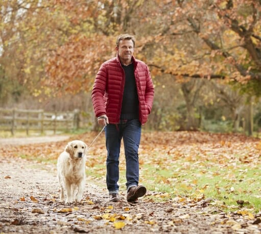 Man out walking his dog to illustrate benefits of Phreesia's Care Pathways for Gastroenterology application