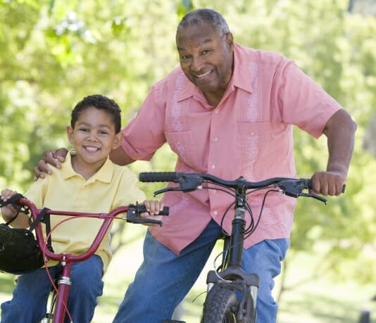 Grandfather and grandson riding bikes to illustrate benefits of Phreesia's Care Pathways for Nephrology application