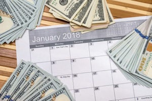 A calendar with 100-dollar bills spread across it to illustrate the use of payment reminders.