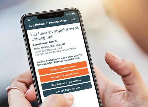 Hands holding a cellphone with the Phreesia Appointment Confirmation screen visible, which allows patients to confirm appointments.
